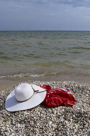 Vintage summer straw beach hat and pareo on the seashore. Accessories for relaxing on the beach. Summer lifestyle. Vacation mood. Stock Photo
