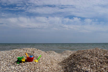 Childs bucket, spade and other toys on tropical beach against sea and blue sky. Stock Photo