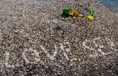 Love sea text on shells beach background. Toys for playing near sea. Relaxation, vacation idyllic concept.