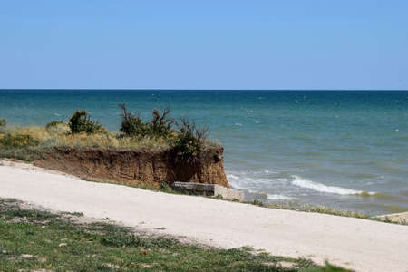 Beautiful summer landscapes with clay cliffs near the sea. Seascape with steep clay cliff