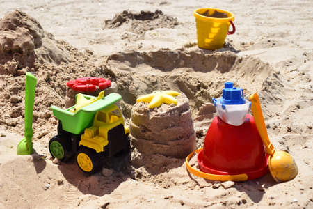 Childrens plastic toys green end yellow car, shovel, yellow and red buckets, green ball with yellow sand on the beach by sea. Childrens beach toys on sand on a sunny day. Sandbox on the playground