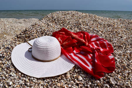 Vintage summer straw beach hat and pareo on the seashore. Accessories for relaxing on the beach. Summer lifestyle. Vacation mood. Stock Photo - 129134768
