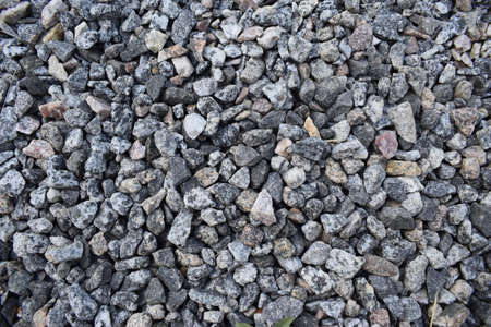 Gravel Rock Texture. Crushed stone and gravel on the ground. Texture background brown stones on a black earth background. Image of broken stones and gravel