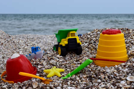 Childs bucket, spade and other toys on tropical beach against sea and blue sky. Plastic childrens toys for sand on the background of the sea. Plastic children toys on the sand beach