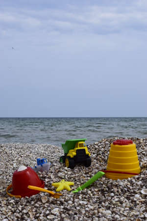Child's bucket, spade and other toys on tropical beach against sea and blue sky. Children's beach toys Stock Photo - 129135062