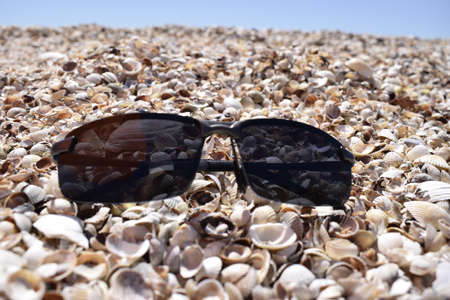 The sunglasses lying on the seashore against the sea. Close up view sunglasses on a sand beach with shells as an elements. Summer vacation concept, accessories for summer beach travel at holidays. Zdjęcie Seryjne - 129135664