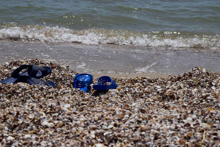 Summer slippers on the beach near the water. Sea shells on a sunny day. Tropical beach vacation and travel concept Stock Photo - 129135751