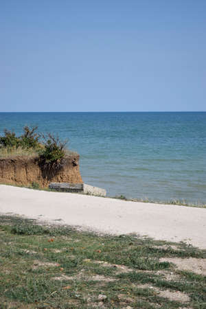 Steep cliff, seashore landscape. Cliff of clay and sea beach. Beautiful summer landscapes with clay cliffs near blue sea.