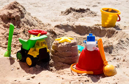 Children's plastic toys green end yellow car, shovel, yellow and red buckets, green ball with yellow sand on the beach by sea. Children's beach toys on sand on a sunny day. Sandbox on the playground Zdjęcie Seryjne - 129136123