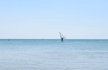 Windsurfing, sailing on the sea in sunny day in summer. Imagens
