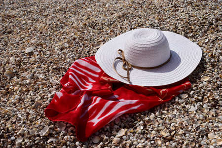 Vintage summer straw beach hat and pareo on the seashore. Accessories for relaxing on the beach. Summer lifestyle. Vacation mood. Imagens