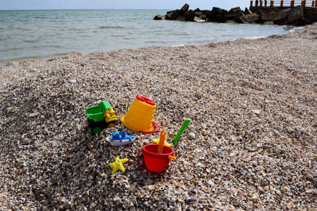 Childs bucket, spade and other toys on tropical beach against sea and blue sky. Imagens