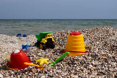 Childs bucket, spade and other toys on tropical beach against sea and blue sky. Childrens beach toys Imagens