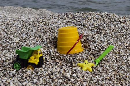 Plastic childrens toys for sand on the background of the sea. Kids toys. Plastic sand toys. Bright toys. Sand construction. Childrens activities. Hobbies and recreation.