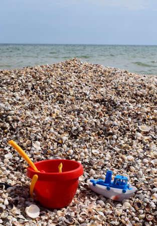 Kids toys, bucket, shovel, car, boat on shells beach, summer background
