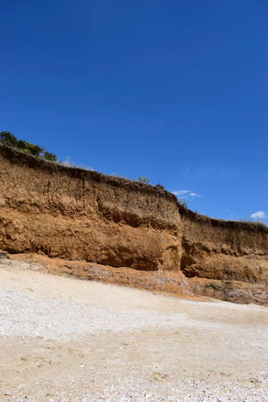 Precipice coast near the sea. The clay cliff on the seashore. Visiting stunning sandy beach. Blue sky with huge red rocks and cliffs