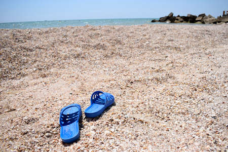 Summer slippers on the beach near the water. Sea shells on a sunny day. Tropical beach vacation and travel concept