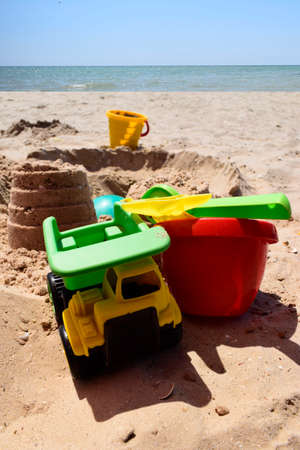 Childrens plastic toys green end yellow car, shovel, yellow and red buckets, green ball with yellow sand on the beach by sea. Childrens beach toys on sand on a sunny day. Imagens