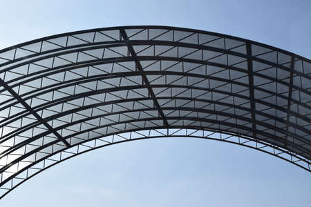 Abstract high-tech architecture background photo, internal structure of glass roof arch. Glass arch of the building with metal frames. Arched glass roof top close up view in modern building. Urban architecture of ceiling.