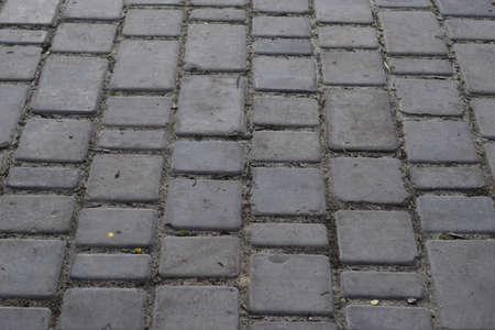 Brick pavement. Gray cobblestone pavement, background photo with perspective effect