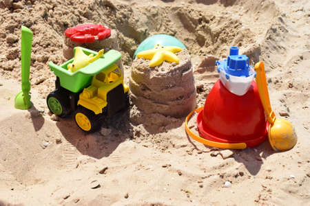 Children's plastic toys green end yellow car, shovel, red bucket, green ball with yellow sand on the beach by sea. Children's beach toys on sand on a sunny day. Sandbox on the playground for games Zdjęcie Seryjne