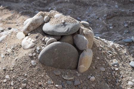Rocks on the sand beach. Closeup of sand and rocks at a beach 免版税图像