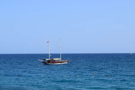 Boat on calm sea water near coast. Tourist boat. Antalya region, Turkey.