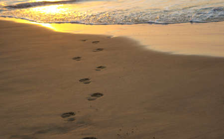 secret place: Footsteps leading into the ocean at sunrise Stock Photo