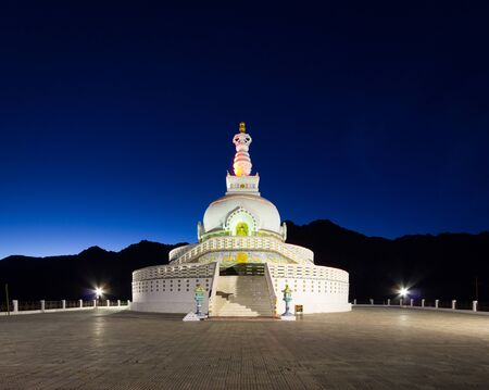 Front view of Shanti Stupa with background of twilight sky and silhouette mountain range. Stock Photo