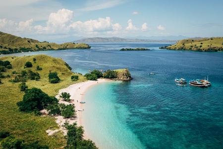 맑은 날의 높은 각도보기 핑크 해변 플로레스 바다와 관광 보트의 청록색 물. 섬은 플로레스, 코모도 제도, 인도네시아에 있습니다. 스톡 콘텐츠