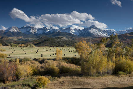 Fall view of hay bales in a field with San Juan Mountain range of the Dallas Divide just outside of Ridgway, Colorado, United States of America