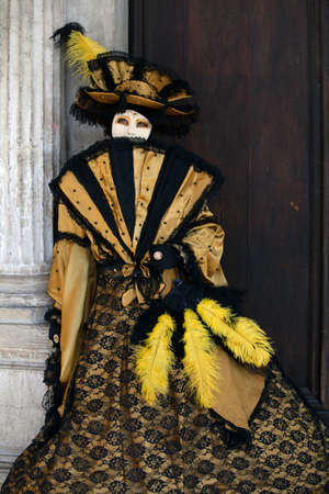 Venetian Carnival Figure in a colourful yellow and black costume and mask Venice Italy