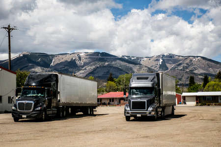 west usa: trailer trucks parking in front of Mountains in the west USA Stock Photo