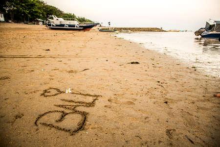 sanur: Bali Indonesia written in sand at Sanur Beach sunset