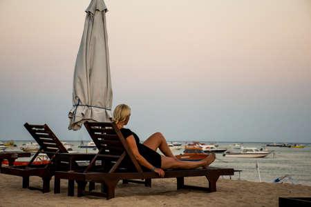sanur: Bali in Indonesia girl sitting at Sanur Beach sunset