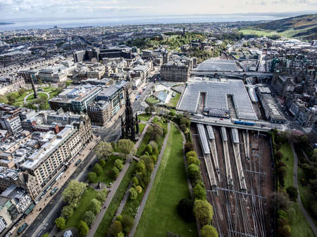 scottish culture: Edinburgh city historic Train Station Rail way on sunny Day Aerial shot Stock Photo