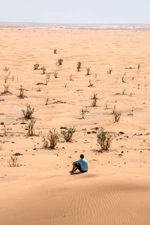 to rub: Man tourist in desert rub al khali in Oman sitting in sand view landscape 3 Stock Photo