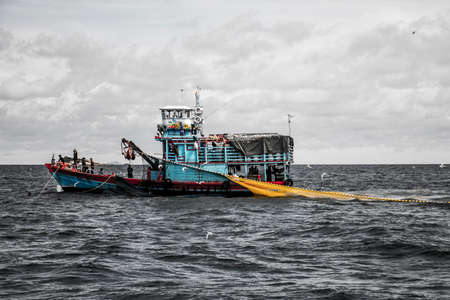 Fishing boat big fishermen with fish net on the blue ocean catch fish Reklamní fotografie