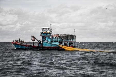 Fishing boat big fishermen with fish net on the blue ocean catch fish Standard-Bild