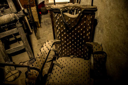 Old medieval torture chamber with chair and tools Stock Photo