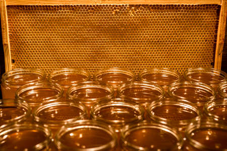 Golden yellow honey in glass jar on wooden board Closeup Copy space comp frame empty textspace