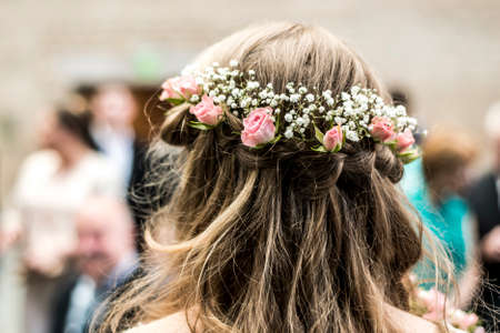 wreath with flowers Rear view blonde bride with a chick coiffure Stock Photo