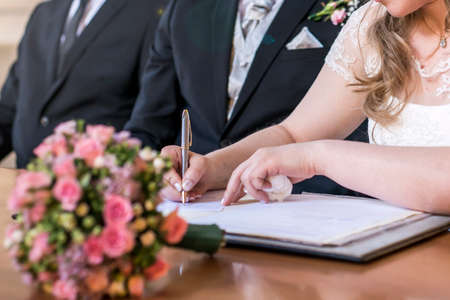 marriage elegant bride signing register, holding pen and official document wedding couple