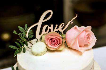 postcard background: Beautiful wedding cake with cream With text Love on top and pink flowers roses Stock Photo