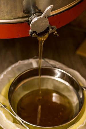 extractie van honing, honing die uit een centrifuge stroomt in een zeef die in een emmer hangt