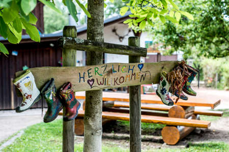 painted wood: Party Label rubber boots sign wooden forest tree house Herzlich Willkommen Means Welcome Stock Photo