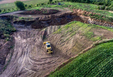 top view heavy machine excavator bagger working in mud on construction site with green landscape surrounding