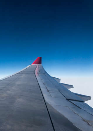 wing of airplane from Air in the sky winglet red colored airline blue sky clouds