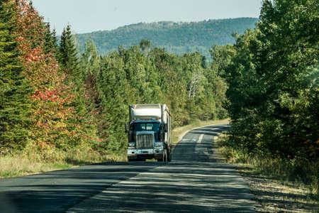 캐나다 온타리오 퀘벡의 깊은 숲에있는 고속도로에서 세미 트럭 스톡 콘텐츠