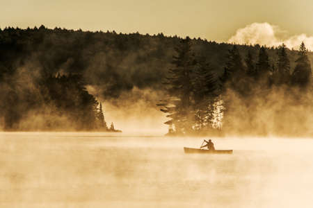 Canada Ontario Lake of two rivers Canoe Canoes foggy water sunrise fog golden hour on water in Algonquin National Park Archivio Fotografico